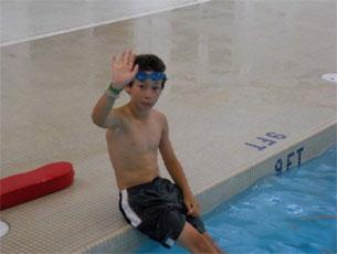 A boy sitting at the edge of a swimming pool on concrete, waving to the camera