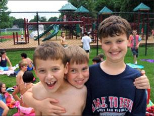 Three boys smiling and arm in arm near a playground with other children drying off in swimwear around them