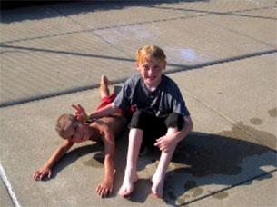 Two boys laying on concrete and drying out, smiling and playing