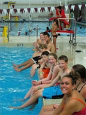 Boys and girls sitting at the edge of a swimming pool with their legs dangling into the water, and a lifeguard at their post