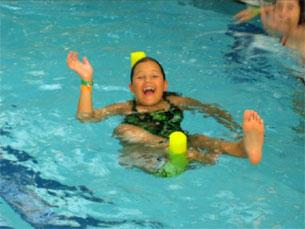 A girl in a swimming pool, waving and floating on a yellow 'pool' noodle flotation toy