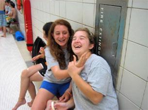 Girls laughing and sitting on a bench at an aquatic facility