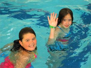 A pair of girls in a swimming pool, smiling and waving at the camera