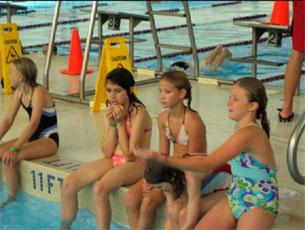 Five girls sitting at the edge of a swimming pool with their legs dangling into the water